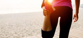 Female runner stretching at beach